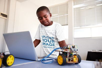 T-Shirt Mockup of a Kid Trying a Robotics Project at School 39098-r-el2