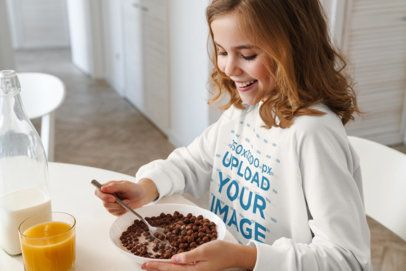 Mockup of a Girl with a Crewneck Sweatshirt Having Breakfast 39409-r-el2