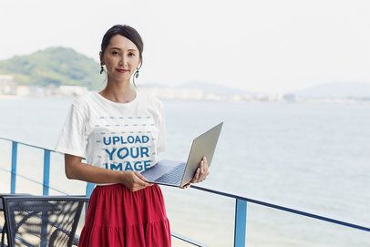 T-Shirt Mockup of a Woman Standing Next to the Ocean with a Computer 39460-r-el2