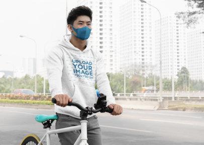 Hoodie Mockup of a Man Walking Down the Street With His Bike 36258-r-el2