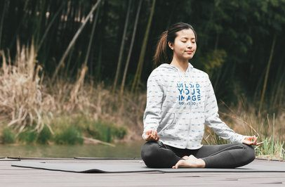 Mockup of a Woman with a Heathered Full-Zip Hoodie Doing Yoga Outside 40100-r-el2