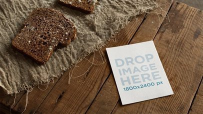 Flyer Lying On Wooden Table With Bread While A Wheat Leaf Passes Stop Motion Mockup a13722