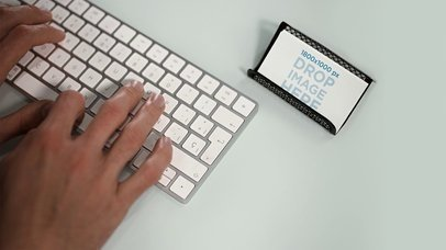 Stop Motion Of Business Cards Lying On Holder In Desktop While A Person Is Writing On iMac Keyboard Mockup a13727
