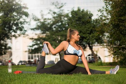 Mockup of an Athletic Woman Wearing a Sports Bra While Stretching on the Grass 35044-r-el2