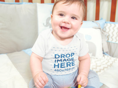 Mockup of a Smiling Baby Boy Sitting in his Crib while Wearing a Onesie a13959