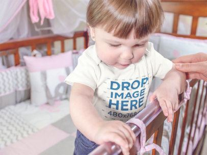 Beautiful Baby Girl Standing On Her Wooden Crib While Wearing A Onesie Mockup 13957