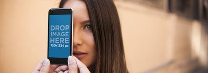 Mockup of a Woman Behind an iPhone in Portrait Position a14034w