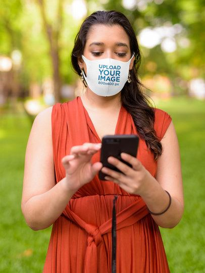 Face Mask Mockup Featuring a Woman Checking Her Phone at a Park 42836-r-el2