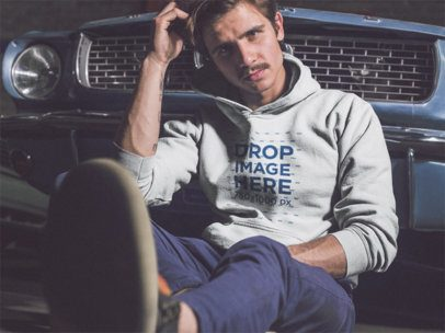White Man Wearing a Pullover Hoodie While Sitting on the Floor Lying Against a Vintage Car Mockup a13612