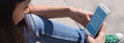Mockup of a Young Girl Using Her iPhone 6 While Sitting Down at the Skate Park a14210wide