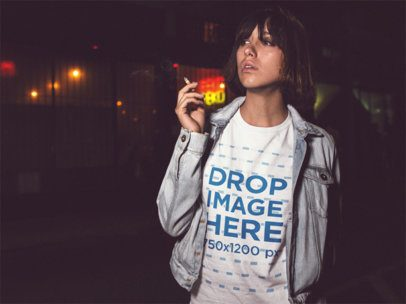 Trendy Girl Smoking in the City at Night While Wearing a Round Neck Tshirt with a Denim Jacket On Top a13564