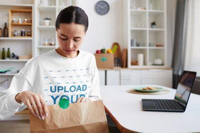 Sweatshirt Mockup Featuring a Woman Opening a Food Bag at Home 41763-r-el2