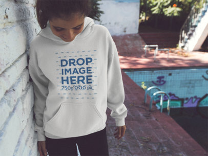 Young Girl Looking at her Feet While Wearing a Pullover Hoodie Near an Abadoned Pool Mockup a12849
