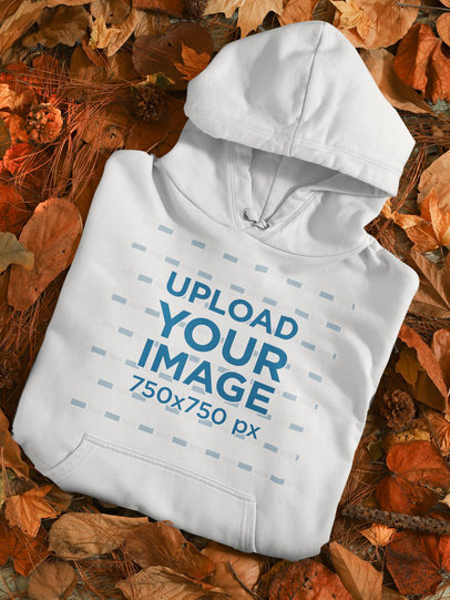 Mockup of a Folded Pullover Hoodie Placed Over Autumn Leaves m132