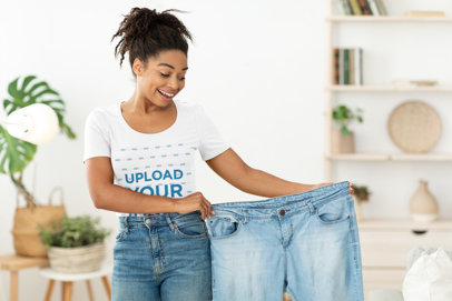 T-Shirt Mockup of a Woman Holding a Pair of Old Jeans 43680-r-el2