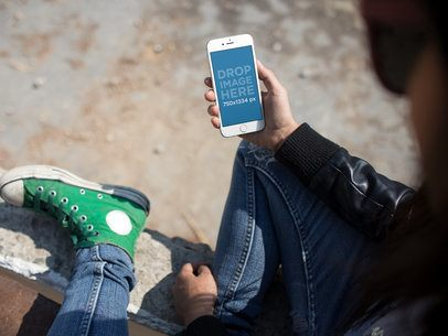 Young Girl Checking her White iPhone 6 While Sitting Down on the Concrete Floor Wearing Green Converse a14212