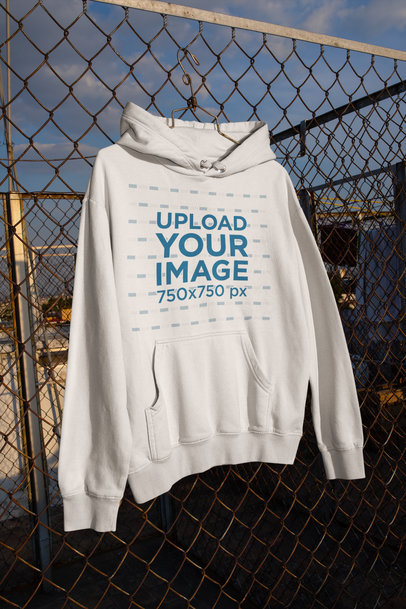 Mockup of a Pullover Hoodie Hanging from a Chainlink Fence m443