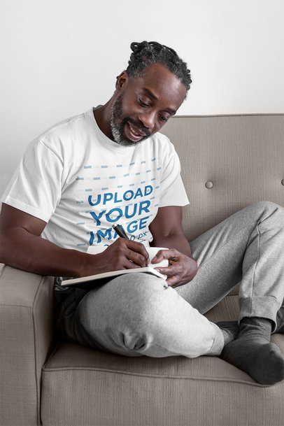 T-Shirt Mockup Featuring a Middle-Age Man Writing at Home 45639-r-el2