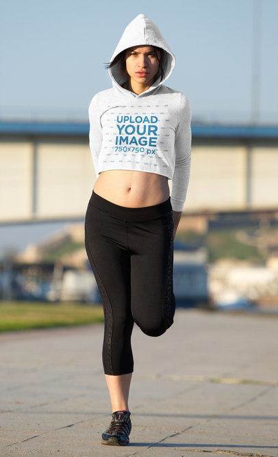 Crop Top Hoodie Mockup Featuring a Serious Woman Stretching Before Running 45224-r-el2