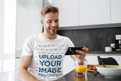 T-Shirt Mockup of a Man Checking His Phone While Having Breakfast 45868-r-el2