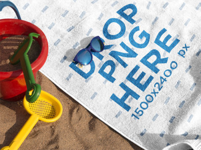 Mockup of a Towel Lying on the Beach with Accessories Near it and Sunglasses a14892