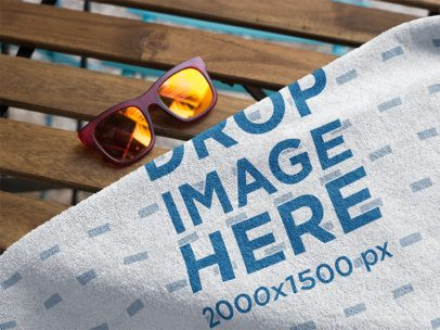 Mockup of a Towel on a Wooden Bench With Sunglasses Near It a14884