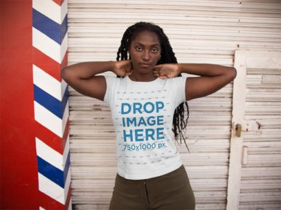 Black Girl Wearing a T-Shirt Mockup While Playing with her Hair Standing Against a Closed Shop a15576