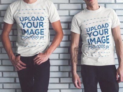 Two Guys Wearing Different T-Shirts Mockup While Lying Cropped Faced Against a White Bricks Wall a15640
