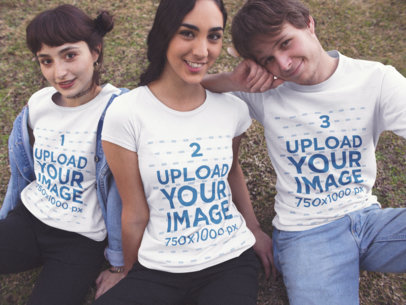 Three Young Friends Sitting Down at a Park While Wearing T-Shirts Template with Different Designs a15693