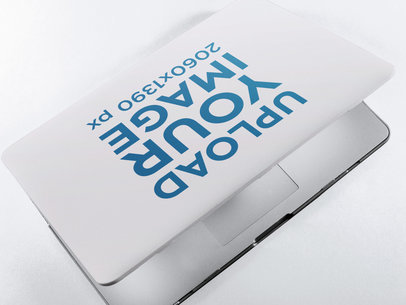 Mockup of a Laptop Cover on a Closing MacBook Lying on a Solid Color Surface a15335
