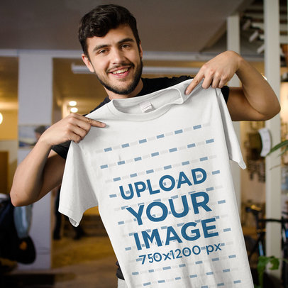New Office Guy Holding a T-Shirt Mockup While Standing Smiling a15616