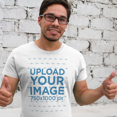 Smiling Young Hispanic Man Wearing a Round Neck Tee Template and Glasses Against a White Bricks Wall a15528