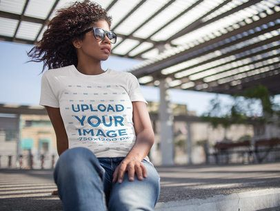Young Girl Wearing Sunglasses and a Tshirt Mockup While Facing the Wind Outdoors a15830