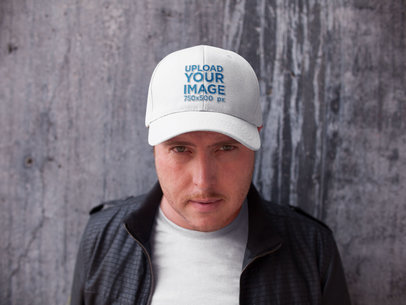Front Shot of a White Guy Wearing a Hat Mockup While Standing Against a Concrete Wall a15872
