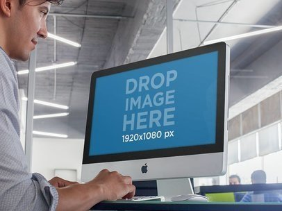 Mockup of a Young Male Intern at an Office Using an iMac a4771