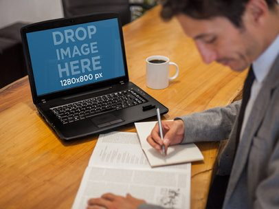 Laptop Mockup Featuring a Businessman at the Office Working on his Laptop a5138
