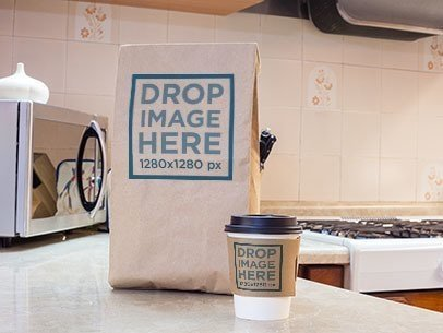 Takeaway Coffee Cup and Paper Bag Mockup on Top of a Kitchen Counter a6698