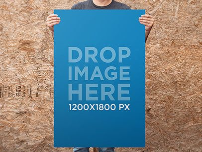 Guy Standing in Front of a Wooden Wall Holding a Poster Mockup a10321
