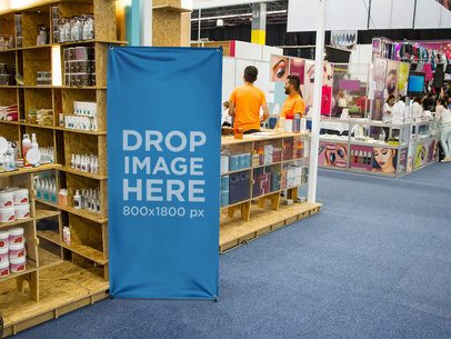 Vertical Banner Mockup Standing Next to a Beauty Stand at a Trade Show a10683