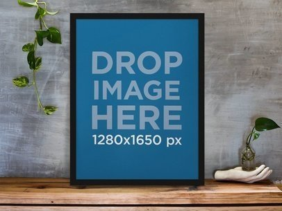 Framed Art Print Standing on a Wooden Desk Against a Concrete Wall Near a Hand Decoration a10403