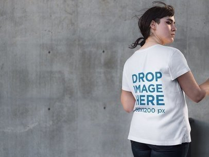 Back of an Alternative Girl Wearing a T-Shirt Mockup while Facing a Concrete Wall a9258b