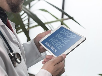 iPad Mockup in Landscape Mode of a Male Doctor Next to a Plant 12397