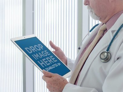 Mockup of a Physician Staring at an iPad in Portrait Position 12448