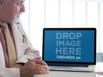 MacBook Mockup of a Senior Doctor Reviewing his Patient Information a12449
