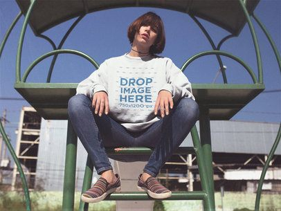 Crewneck Mockup of a Young Asian Woman with Short Hair Sitting on a Green Ladder a12654
