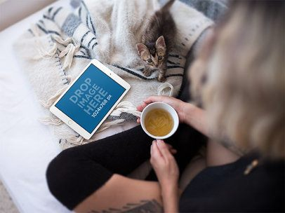 Mockup of a Woman in Bed Watching Her iPad Mini and Holding a Coffee Cup a12809