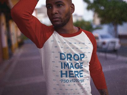 Young Black Man Posing in the Street with a 3/4 Sleeve Raglan T-Shirt Mockup a12552