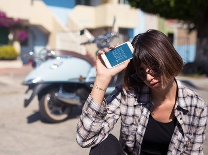 iPhone Mockup in Portrait Position Featuring a Woman with a Vintage Scooter in the Background 12954b