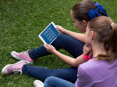 Mockup of Two Girls Playing with a White iPad Mini in Landscape Position in their Garden 13002