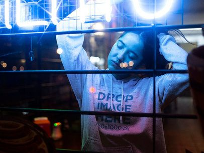 Pretty Asian Woman with Long Hair Wearing a Hoodie Mockup at a Cafe with Neon Lights a12714